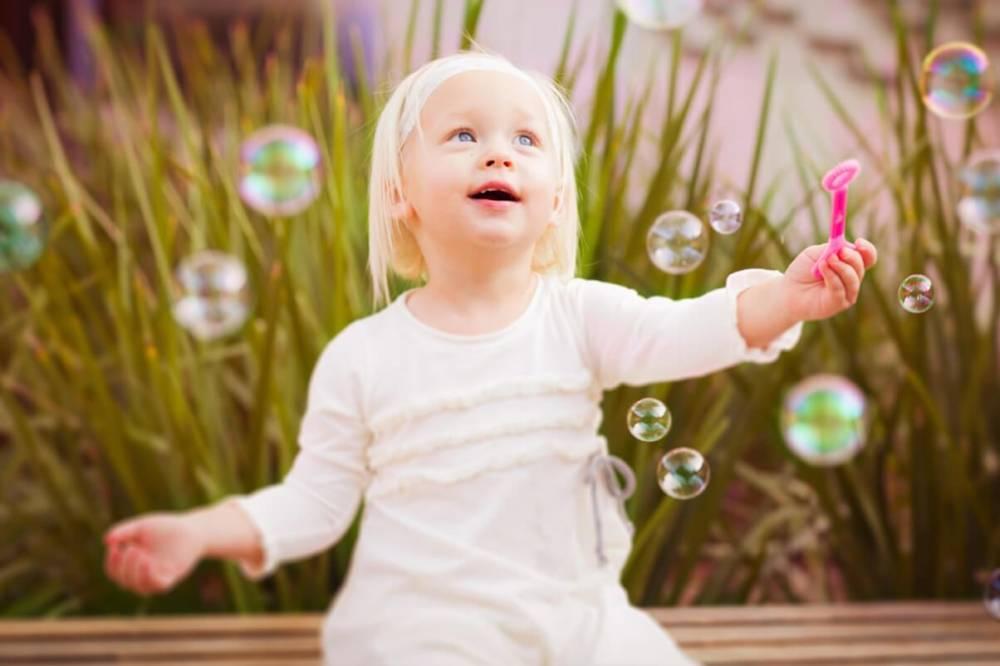 Abbildung zeigt ein Kind beim Spielen mit Seifenblasen